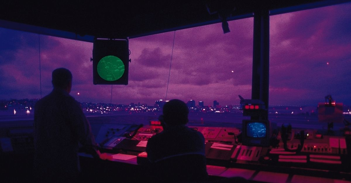 Air traffic controlling booth with two air traffic dispatchers with a purple sunset shining through windows.