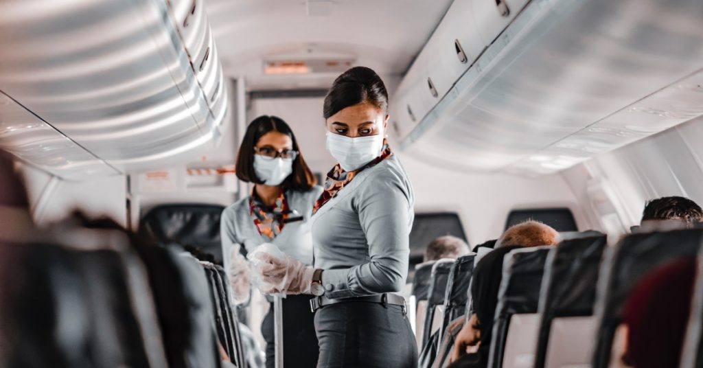 airline attendant wearing mask on crowded flight