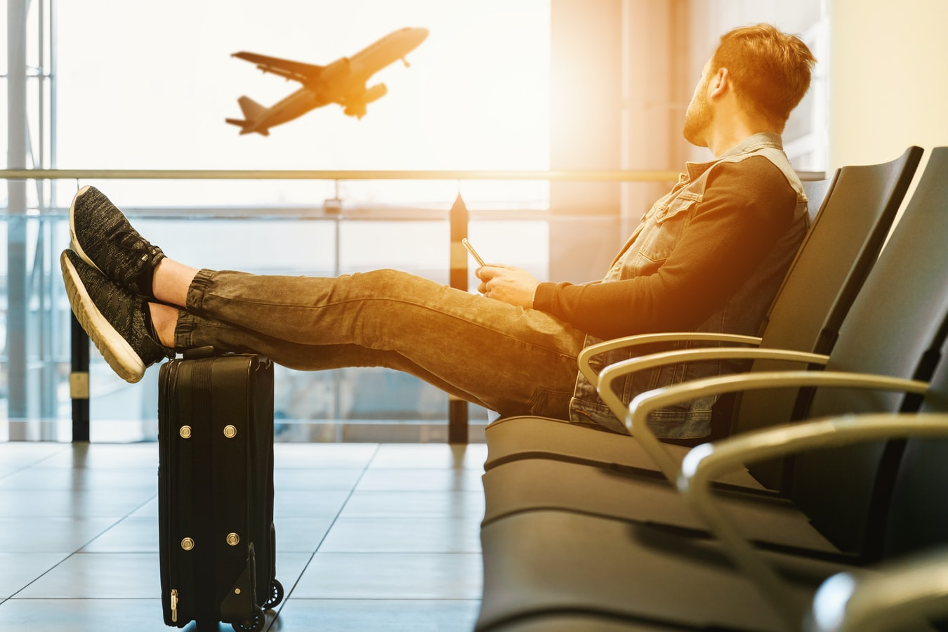 man at airport looking at plane take off