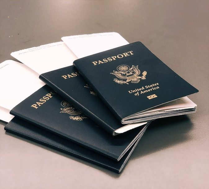 3 passports with plane tickets sticking out